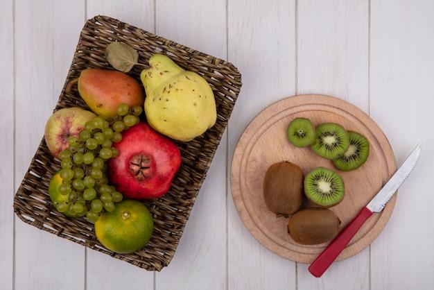 Vista dall'alto kiwi con un coltello su un tagliere con mandarini melograno pera mela e uva in un cesto su un muro bianco