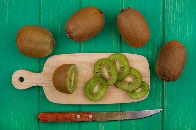 Kiwi vista dall'alto con fette sul tagliere e coltello su sfondo verde