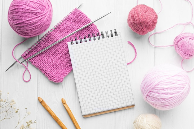 Top view of knitting set with notebook and needles