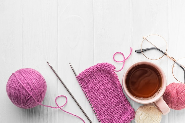 Top view of knitting set with yarn and tea