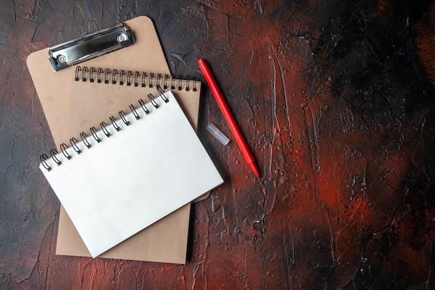 Vista dall'alto dei quaderni a spirale kraft con penna su sfondo scuro