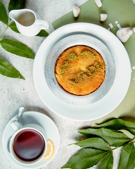 Top view of kunefe plate turkish dessert served with tea