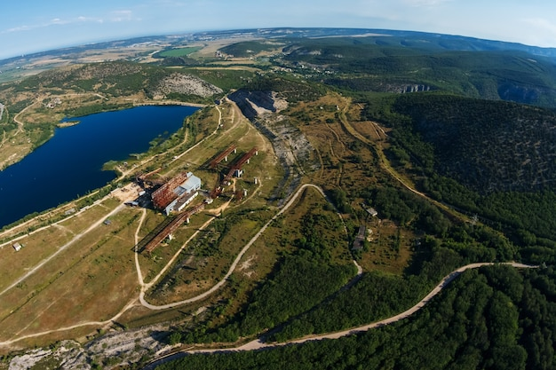 Top view of the lake and forests dirt roads on a sunny summer day a birds eye view of the earth beau...