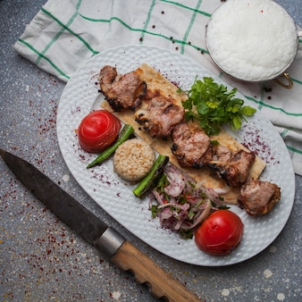 Top view lamb kebab with fried vegetables and chopped onion and ayran and knife in white plate