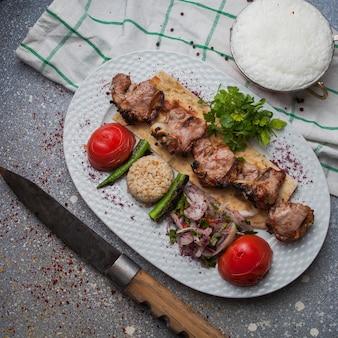 Vista dall'alto kebab di agnello con verdure fritte e cipolla tritata e ayran e coltello nel piatto bianco
