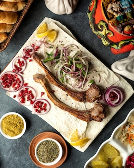 Vista dall'alto di costolette di agnello kebab con erbe cipolla e fagioli di melograno su lavash