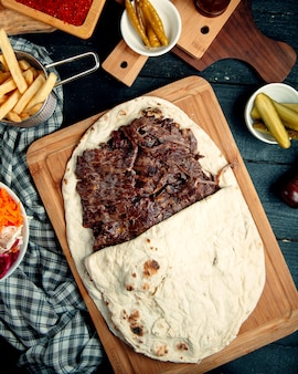 Top view of lamb steak doner in flatbread served with fries and pickled cucumber