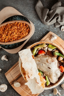 Top view of lamb stew pot covered with flatbread served with bulgur