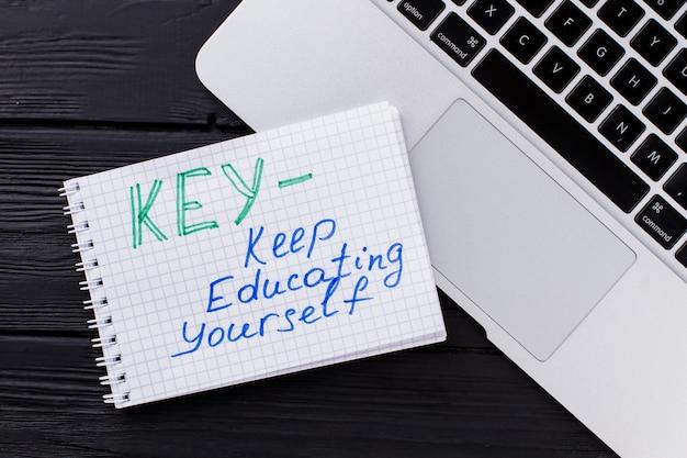 상위 뷰 노트북 및 약어가 있는 메모장입니다. 핵심 - 계속 자신을 교육하십시오. 어두운 나무 배경입니다.