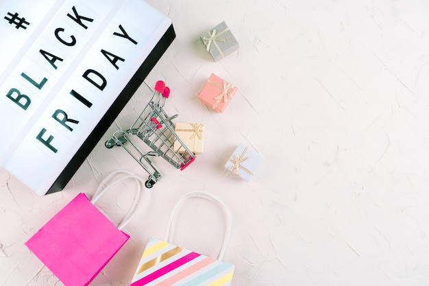 Top view of laptop, black friday promotion sale words on lightbox, gift boxes and trolley. flat lay