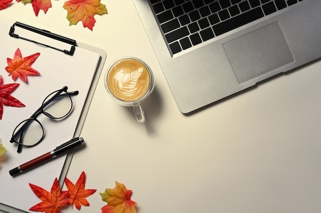 Top view laptop computer, coffee cup, glasses and autumn maple leaves on white background.