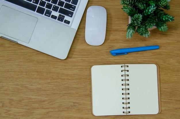 Вид сверху портативный компьютер, мышь, цветок, блокнот и ручка на деревянном столе. плоская копия spce. работа для дома