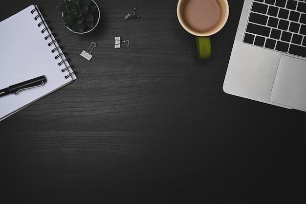 Вид сверху портативный компьютер, ноутбук и кофейная чашка на черном столе.