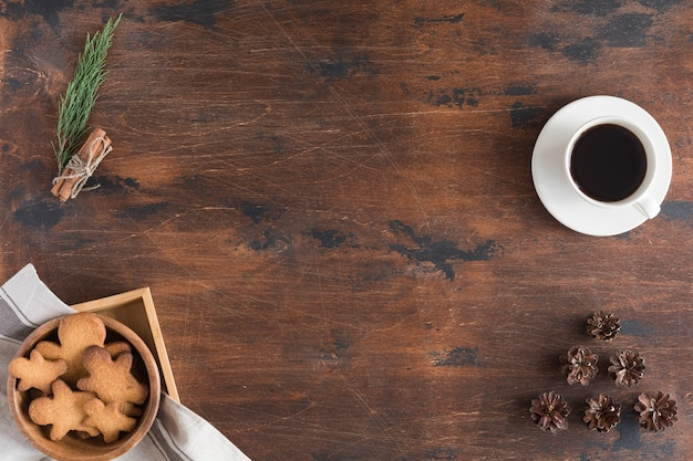 Top view of laptop, gingerbread man, cup of coffee on dark rustic wooden background