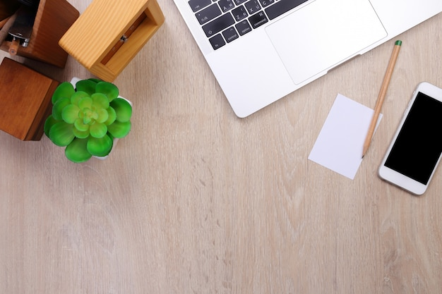 Top view laptop, smartphone and office stationery with wooden background