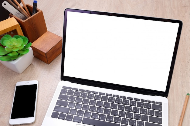 Top view laptop with blank screen, smartphone and office stationery