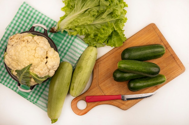 Top view of large white cauliflower on a bowl on a green checked cloth with cucumbers on a wooden kitchen board with knife with zucchinis and lettuce isolated on a white surface