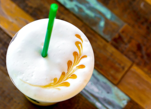 Top view of latte art on ice latte's milk froth and old wooden .