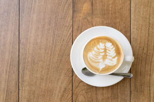 Top view of latte coffee or cappuccino coffee in white cup with beautiful tree latte art