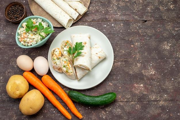 Вид сверху сэндвич-рулетов из лаваша, нарезанных салатом и мясом внутри вместе с салатом вместе с овощами на деревянном столе сэндвич с закусками