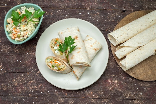 Top view lavash sandwich rolls sliced with salad and meat inside along with salad on the wooden desk snack food meal sandwich