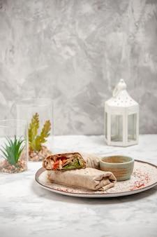 Vista dall'alto di involucro di lavash e yogurt in una piccola ciotola su un piatto e una casa giocattolo sulla superficie bianca macchiata