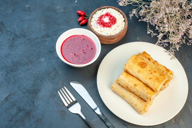 Vista dall'alto degli involucri di lavash su un piatto e posate formaggio grattugiato sul lato sinistro su sfondo nero
