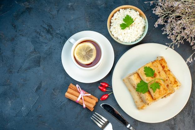 Vista dall'alto di involtini di lavash su un piatto servito con set di posate verdi e formaggio grattugiato in una ciotola lime alla cannella una tazza di tè nero al limone su sfondo nero