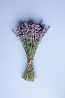 Top view lavender flowers in a bunch on a blue space vertical photo