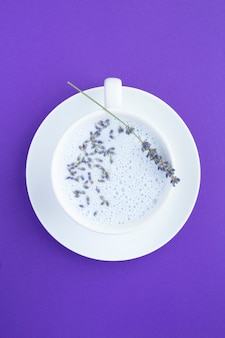 Top view of lavender moon milk in the white cup on the violet surface