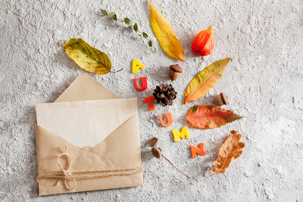 Top view of layout with word autumn, envelope mock up and fallen leaves. autumn concept