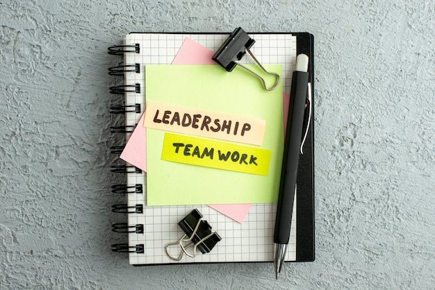 Vista dall'alto del lavoro di squadra di leadership su buste colorate su quaderno a spirale e libro su sfondo grigio sabbia