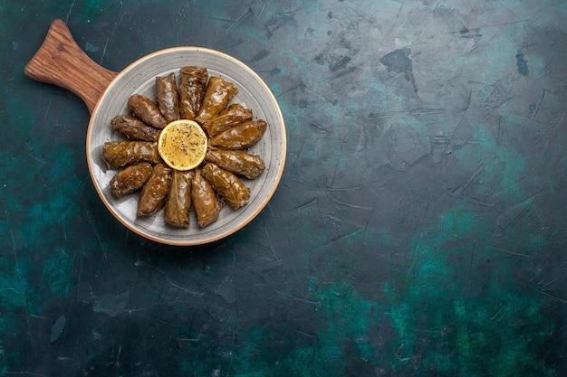 Vista dall'alto foglia dolma delizioso pasto di carne orientale arrotolato all'interno di foglie verdi sulla scrivania blu scuro pasto a base di carne cibo cena piatto verdura salute caloria