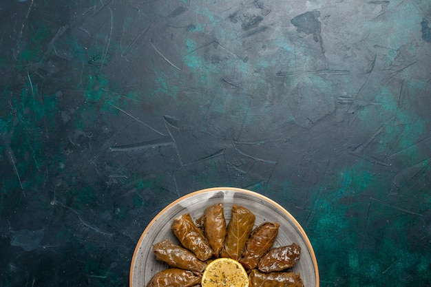 Vista dall'alto foglia dolma delizioso pasto di carne orientale arrotolato all'interno di foglie verdi sulla scrivania blu scuro pasto a base di carne cibo cena piatto verdura salute calorie