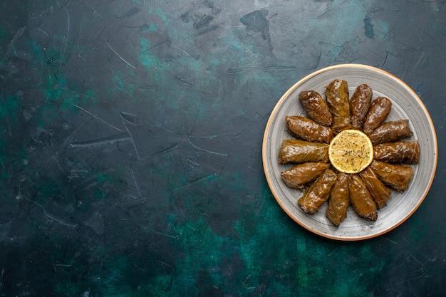 Вид сверху листовая долма вкусная восточная мясная еда, завернутая в зеленые листья на темно-синем столе, мясная еда, ужин, овощ, здоровье, калорийность, блюдо