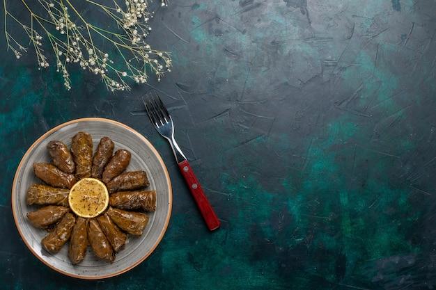 상위 뷰 잎 돌마 맛있는 동부 고기 식사 파란색 책상에 녹색 잎 안에 압연 고기 음식 저녁 식사 요리 야채 건강