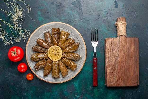 Vista dall'alto foglia dolma delizioso pasto di carne orientale arrotolato all'interno di foglie verdi con pomodori freschi sulla scrivania blu carne cibo cena piatto salute vegetale