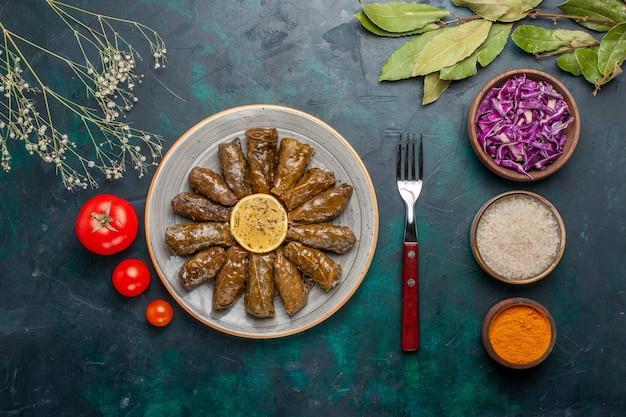 Vista dall'alto foglia dolma delizioso pasto di carne orientale arrotolato all'interno di foglie verdi con pomodori freschi sulla scrivania blu scuro carne cibo cena piatto salute vegetale