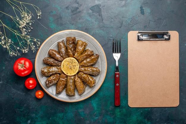 Вид сверху листовая долма вкусная восточная мясная еда, завернутая в зеленые листья со свежими помидорами на синем столе, мясная еда, обед, блюдо, здоровье овощей