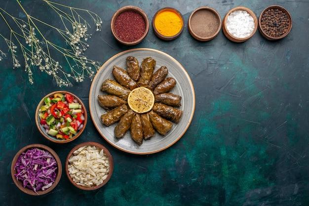 상위 뷰 잎 돌마 맛있는 동부 고기 식사 파란색 책상 고기 저녁 식사 요리 건강 식사에 조미료와 얇게 썬 야채와 함께 녹색 잎 안에 압연