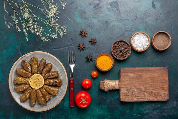 Vista dall'alto foglia dolma delizioso pasto di carne orientale arrotolato all'interno di foglie verdi con condimenti sulla scrivania blu carne cibo cena piatto vegetale salute pasto