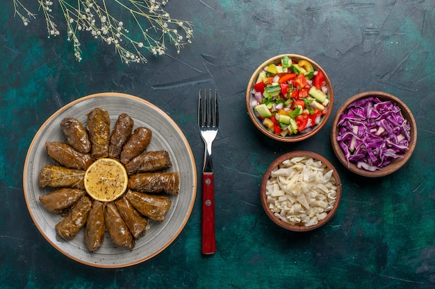 Vista dall'alto foglia dolma delizioso pasto a base di carne orientale arrotolato all'interno di foglie verdi con verdure a fette sul pasto di salute vegetale piatto cena a base di carne scrivania blu
