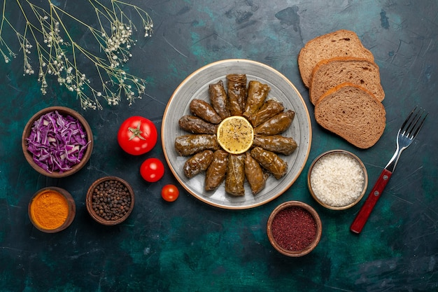 Вид сверху листовая долма вкусная восточная мясная еда, завернутая в зеленые листья с помидорами и хлебом на синем столе, мясная еда, обеденное блюдо, здоровье овощей