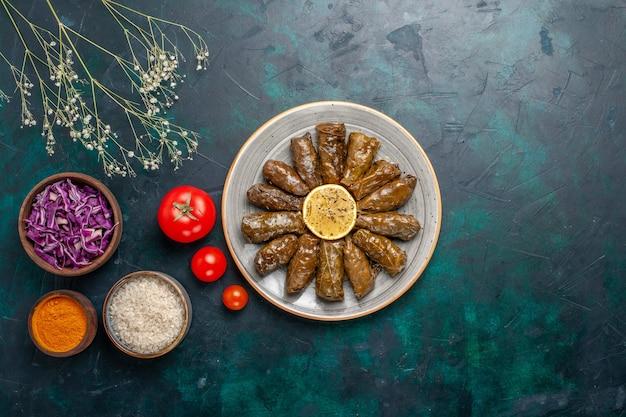 Vista dall'alto foglia dolma delizioso pasto di carne orientale arrotolato all'interno di foglie verdi con pomodori e condimenti sulla scrivania blu carne cibo cena piatto salute vegetale