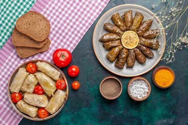 Vista dall'alto foglia dolma farina di carne orientale arrotolata all'interno di foglie verdi con pane e cavolo dolma sulla scrivania blu scuro carne cena piatto pasto orientale