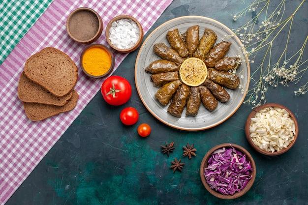 Vista dall'alto foglia dolma farina di carne orientale arrotolata all'interno di foglie verdi con pane sulla superficie blu scuro carne cena piatto orientale pasto
