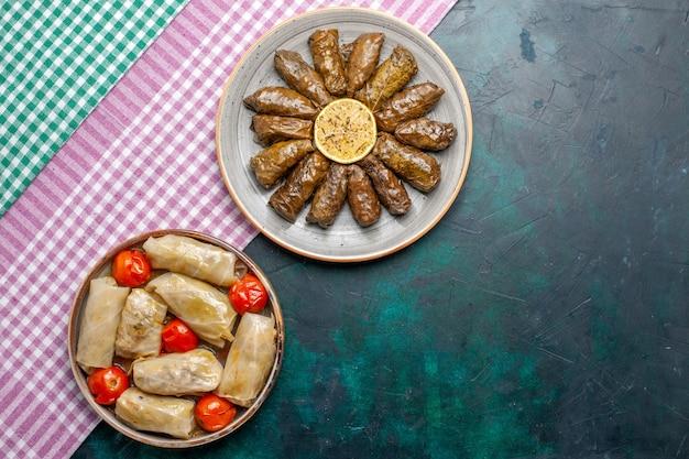 Vista dall'alto foglia dolma farina di carne orientale arrotolata all'interno di foglie verdi con cavolo dolma sulla scrivania blu carne cena piatto orientale pasto calorico