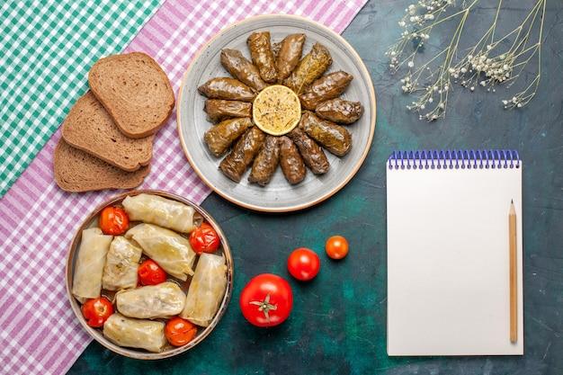 Vista dall'alto foglia dolma farina di carne orientale arrotolata all'interno di foglie verdi con dolma di cavolo e pane sulla scrivania blu carne cena piatto orientale pasto calorie