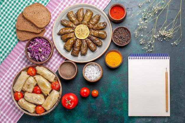 Вид сверху листовой долмы восточное мясное блюдо в зеленых листьях с приправами и капустной долмой на темно-синем столе мясное обеденное блюдо восточная еда