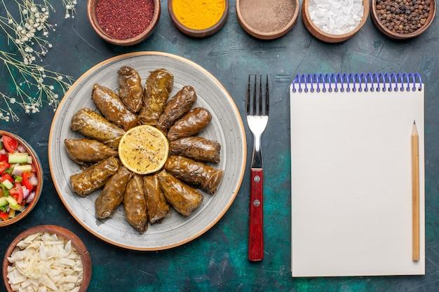 Vista dall'alto foglia dolma farina di carne orientale arrotolata all'interno di foglie verdi con condimenti e verdure a fette sulla scrivania blu cena a base di carne piatto pasto salutare